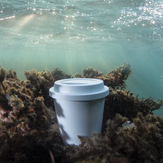 copo de pla compostável com tampa no oceano